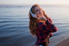 Красивый музыкальный фан девушки танцуя слушая нот к Портрет на предпосылке моря Стоковая Фотография