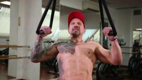 Красивый, мышечный атлетический человек затягивает на веревочках смертной казни через повешение, увеличивая мышцы видеоматериал