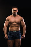 Красивый мышечный культурист представляя на черной предпосылке Стоковая Фотография RF