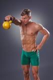 Красивый мышечный человек делая тренировку колокола чайника для плеч Стоковые Фотографии RF