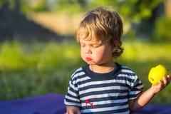 Красивый младенец есть яблоко outdoors Стоковые Изображения RF