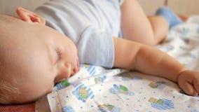 Красивый младенец спать в смешном представлении на кровать Под пеленкой младенца, мальчик около год видеоматериал