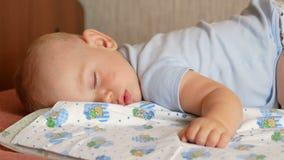 Красивый младенец спать в смешном представлении на кровать Под пеленкой младенца, мальчик около год акции видеоматериалы