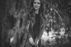 Красивый неподдельный мистик дамы с курчавыми волосами брюнет и прелестными глазами одел в причудливых стильных теплых одеждах с  Стоковая Фотография