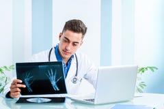 Красивый доктор рассматривая рентгеновские снимки на столе Стоковые Фото