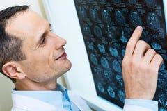 Красивый доктор сравнивая результаты томографии компьютера Стоковая Фотография RF