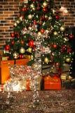Красивый олень рождества с накалять освещает на ноче в живущей комнате с украшенной рождественской елкой, подарками Просторная кв стоковые изображения rf