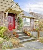 Красивый дом кирпича с красной входной дверью Стоковые Фотографии RF