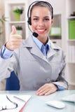Красивый оператор телефона поддержки в шлемофоне на рабочем месте стоковые фото