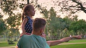 Красивый отец держит малый пункт дочери, матери и девушки на что-то, концепции семьи сток-видео