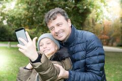 Красивый отец с милой белокурой дочерью делает selfie стоковое изображение