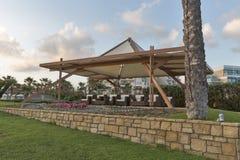 Красивый павильон для релаксации на пляже моря на заходе солнца Стоковые Изображения