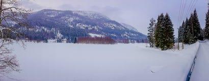 Красивый панорамный взгляд ландшафта пейзажа зимы принятый от одной стороны дороги, покрытой с снегом и льдом в Стоковое Фото