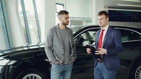 Красивый парень говорит к менеджеру автосалона в мотор-шоу обсуждая новую модель автомобиля, торговца держит видеоматериал