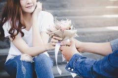 Красивый парень дает красивый букет цветка к его bea стоковая фотография