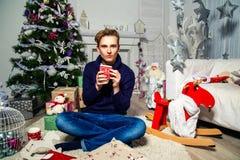 Красивый парень держа чашку в комнате около рождественской елки ново Стоковые Изображения RF