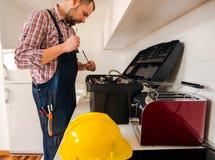 Красивый парень ища его инструмент в кухне Стоковая Фотография RF