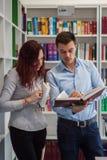 Красивый парень и красивая девушка redhead изучая в библиотеке стоковые изображения rf