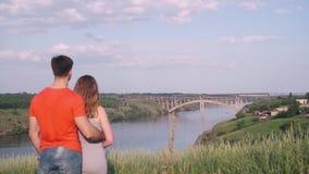 Красивый парень обнимая девушку от задней части и они оба обхватывают вниз на природе, мосте t видеоматериал