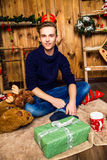 Красивый парень он сидящ и усмехающся в комнате с рождеством Стоковое фото RF