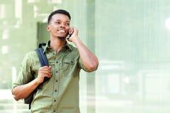 Красивый парень с рюкзаком говоря на сотовом телефоне стоковое изображение rf