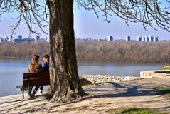Красивый парк на солнечном, день Kalemegdan ` s зимы - 2 любовника сидя на стенде Стоковые Изображения