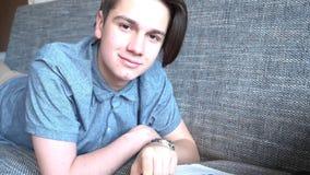 Красивый подросток мальчика говоря на телефоне сидит на серой софе Стоковые Изображения RF