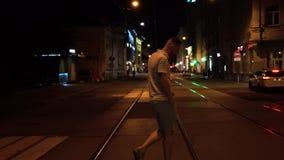Красивый подходящий бородатый человек в striped поло и зеленые шорты пересекают дорогу вечером на crosswalk сток-видео