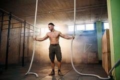 Красивый подходящий человек разрабатывая с веревочками сражения на спортзале стоковое изображение