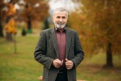 Красивый пожилой человек нося стекла использует телефон прогулка парка осени Стоковая Фотография