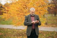 Красивый пожилой человек нося стекла использует телефон прогулка парка осени Стоковая Фотография RF