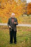 Красивый пожилой человек нося стекла использует телефон прогулка парка осени Стоковые Изображения