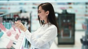 Красивый покупатель девушки брюнета выбирает губную помаду в магазине косметик, замедленном движении акции видеоматериалы