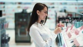 Красивый покупатель девушки брюнета выбирает косметики в магазине видеоматериал