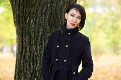 Красивый портрет девушки стоя близко дерево в осени внешней, парк города с желтым цветом выходит на предпосылку, сезон падения, о Стоковое Изображение