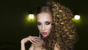 Красивый портрет женщины на черной предпосылке Очарование составляет и длинное вьющиеся волосы стоковые фото