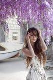 Красивый портрет молодой женщины над цветением глицинии привлекательностей стоковое фото