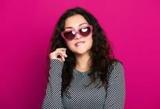 Красивый портрет очарования девушки на пинке в солнечных очках формы сердца, длинном вьющиеся волосы Стоковое Изображение