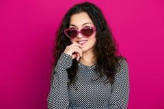 Красивый портрет очарования девушки на пинке в солнечных очках формы сердца, длинном вьющиеся волосы Стоковая Фотография