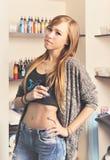 Красивый портрет художника татуировки молодой женщины с машиной татуировки против бутылок чернил татуировки Стоковые Изображения