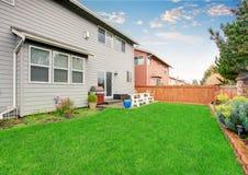 Красивый поставленный задний двор с патио и загородкой Стоковые Фото