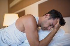 Красивый потревоженный человек имея головную боль лежа на белой кровати B Стоковое Изображение
