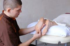 Красивый практикуя masseur замешивает ноги женского клиента, которые li Стоковое фото RF