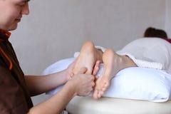 Красивый практикуя masseur замешивает ноги женского клиента, которые li Стоковое Фото