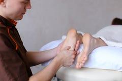Красивый практикуя masseur замешивает ноги женского клиента, которые li Стоковое Изображение RF