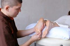 Красивый практикуя masseur замешивает ноги женского клиента, которые li Стоковые Изображения RF