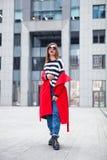 Красивый представлять брюнет внешний красное пальто, striped пуловер, джинсы и солнечные очки моды Яркие красные губы Стоковые Изображения