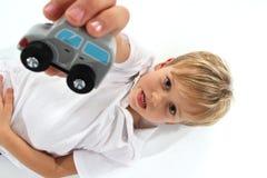 Красивый прелестный справедливый мальчик волос показывая деревянную игрушку автомобиля и делая особенную лицевую ориентацию стоковое изображение rf