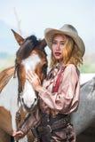 Красивый принимать девушки Азии заботит ее лошадь с любовью и заботить стоковая фотография