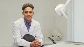 Красивый профессиональный дантист представляя на его офисе видеоматериал